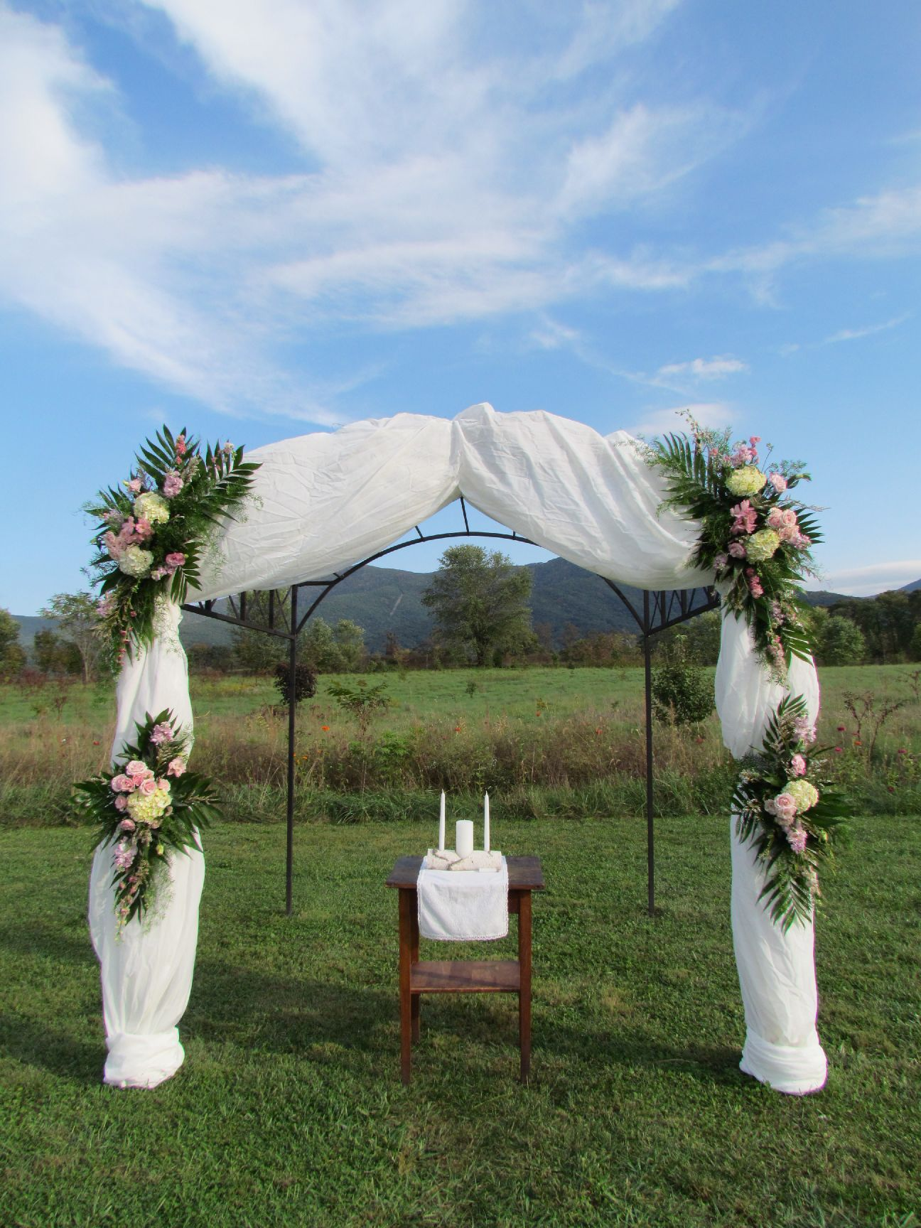 Decorated Arbor Using Sheers And Flower Arrangements This Look