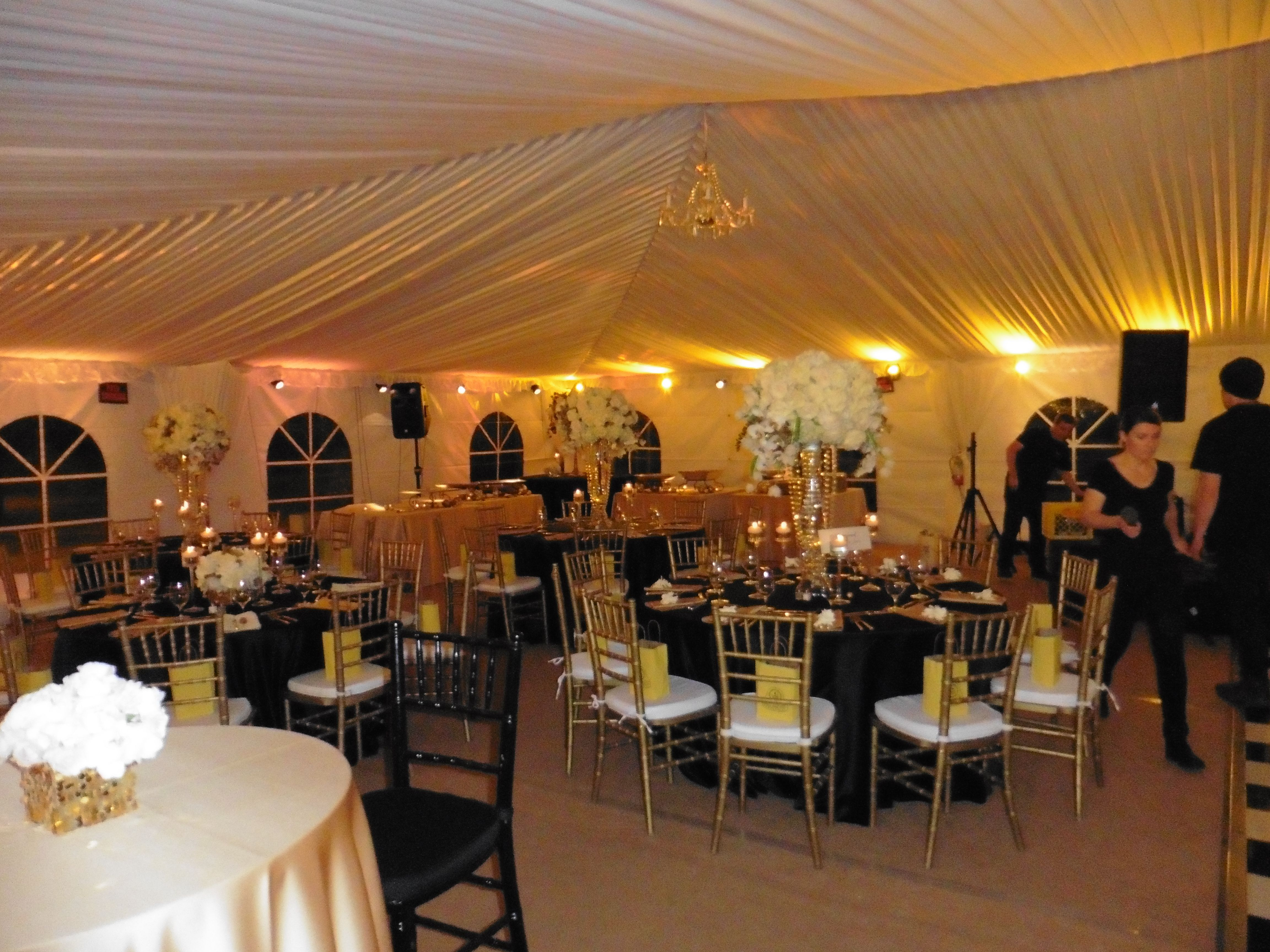 Guest tables in black satin. Swagged tent ceiling. Chandelier.
