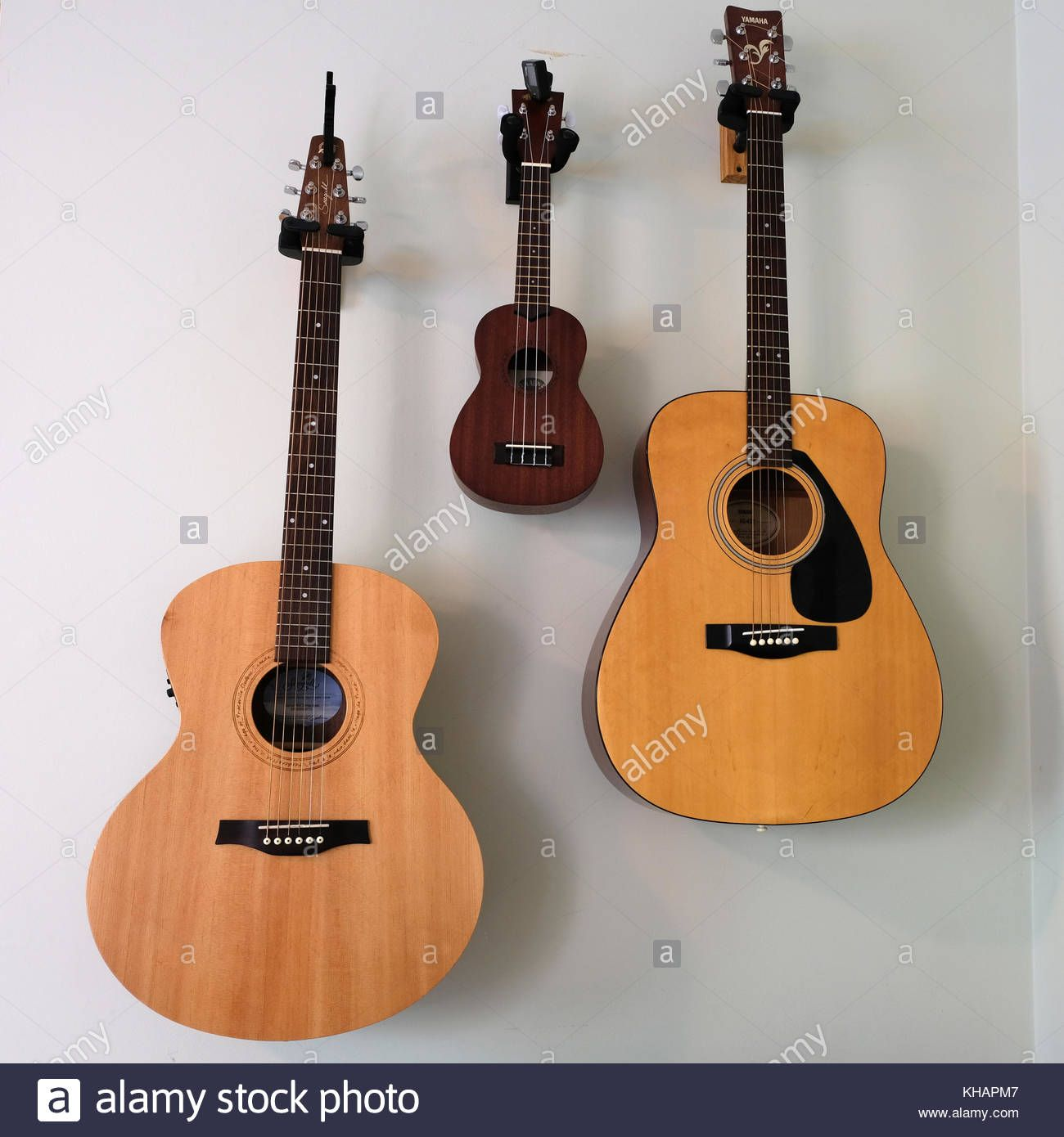 Download This Stock Image Two Guitars And One Banjo Hanging On Wall In Symmetrical Placement Of Musical Instruments Khapm7 Banjo Musical Instruments Guitar