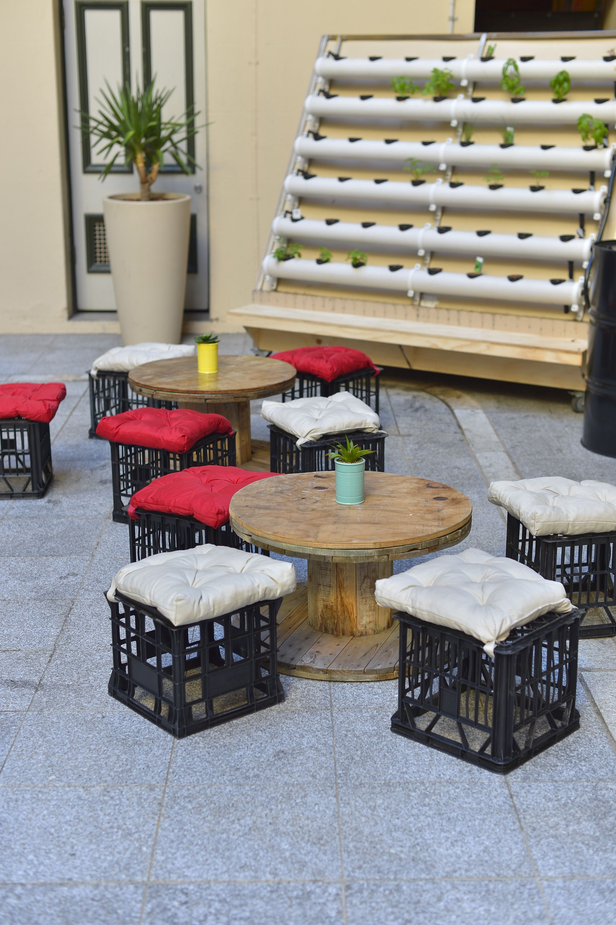 Balkonhocker Spool Coffee Tables With Milk Crate Seats In Front Of A Herb Wall