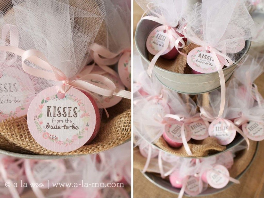 rustic pink bridal shower kisses from the bride to be favors of eos lip balm wrapped up in tulle and tied with a bow