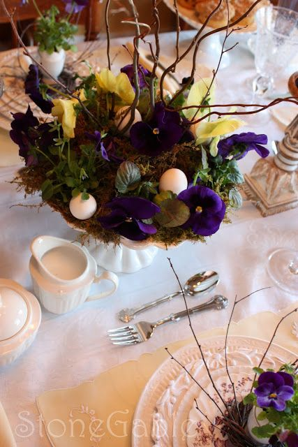 Spring Table the twigs and eggs in centerpeice are carried and repeated on plates in twig wreath and egg cup holder w/pansies and egg next to holder