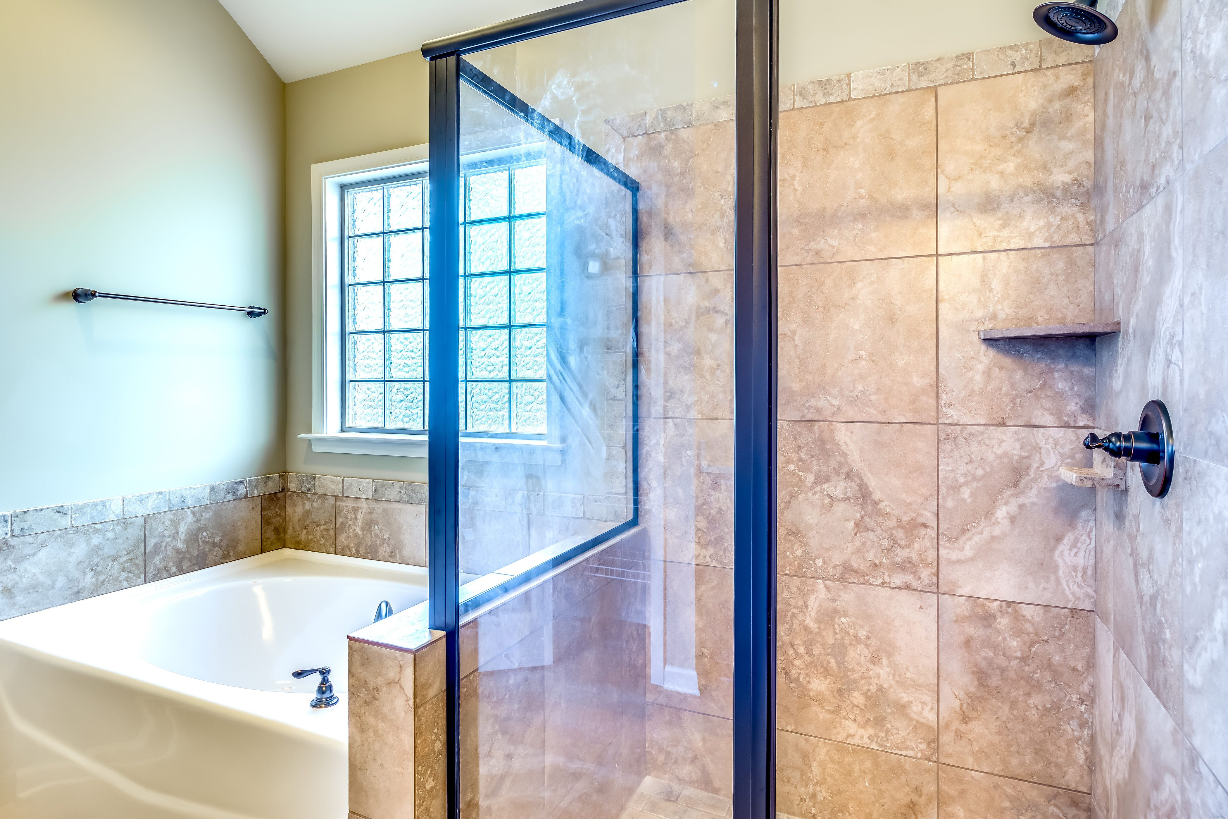 Beautiful bathroom with tan walls along with a spacious bathtub and ...