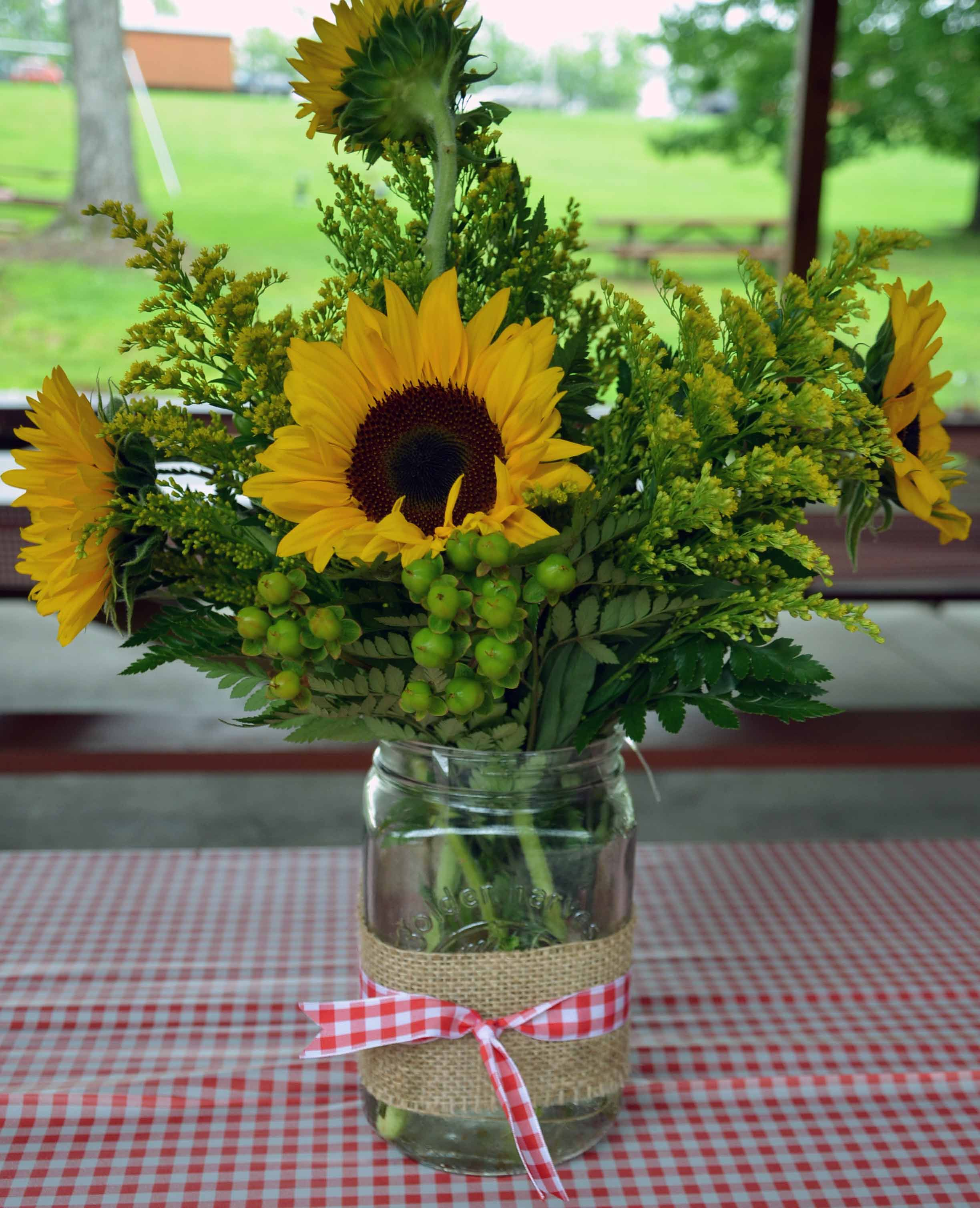 Center pieces sunflowers mason jars red gingham and