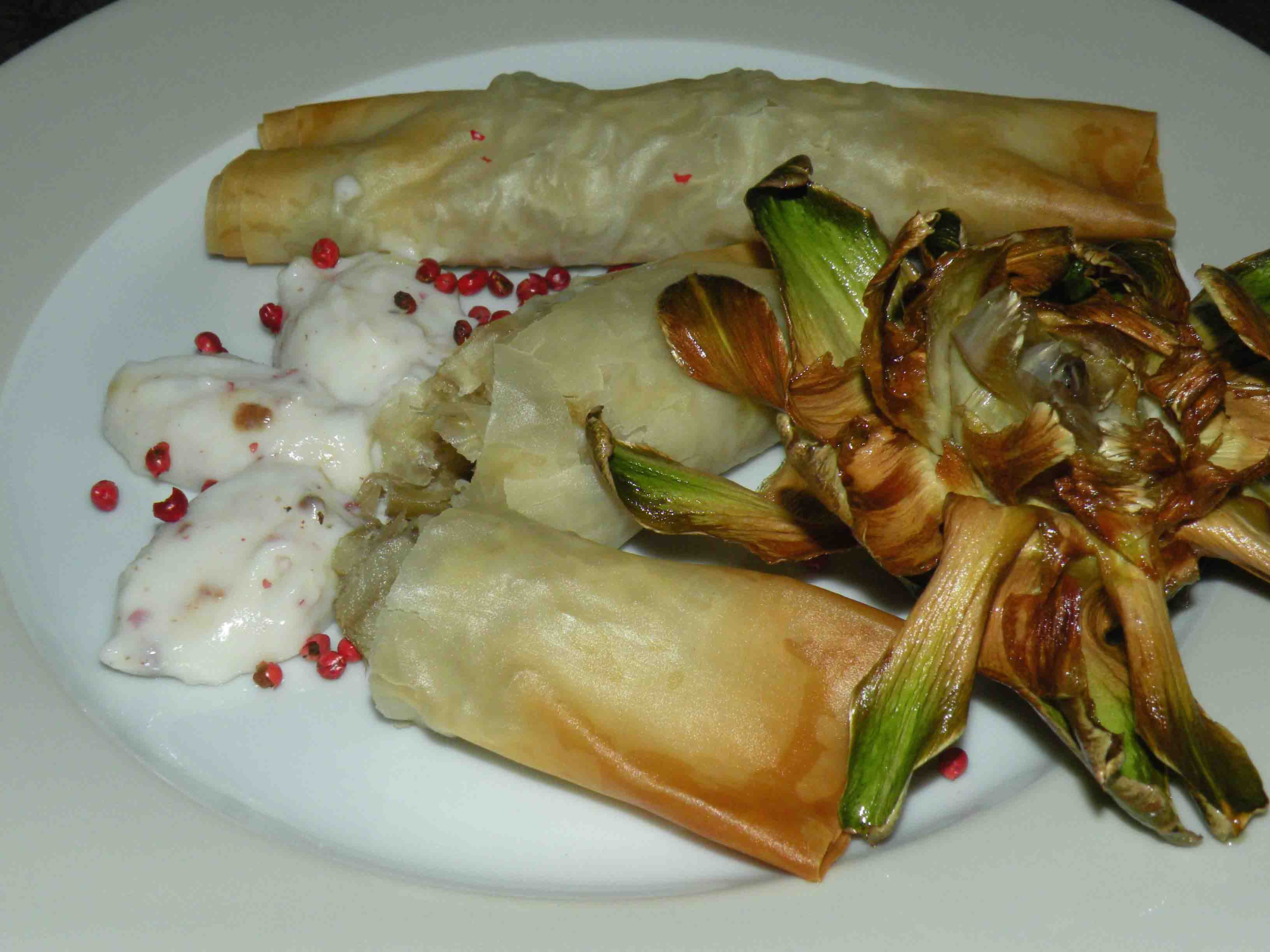 Rolls of phyllo dough filled with perch artichokes and zucchini with cream and pink pepper