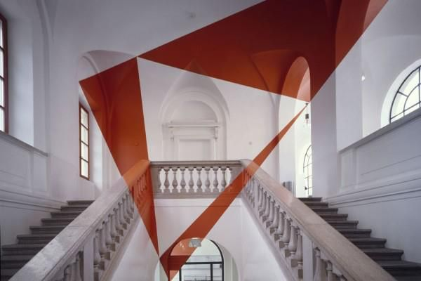 Felice Varini. The swiss artist felice varini creates installations with optical illusion paintings on architectural spaces. the visitors notice geometric, monocolor shapes stretching and sprawling across the room but if they walk around and explore the space, they notice that the shapes change.