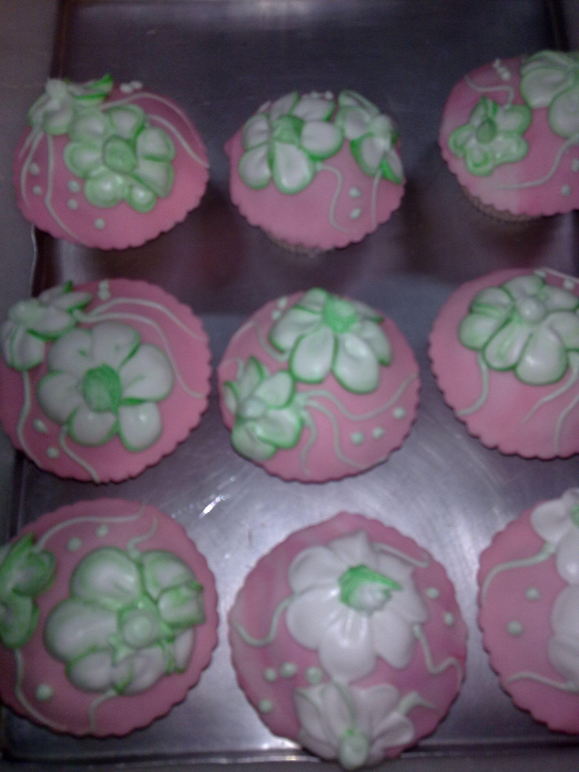 Cupcakes en tono rosa con flores blancas y verdes.