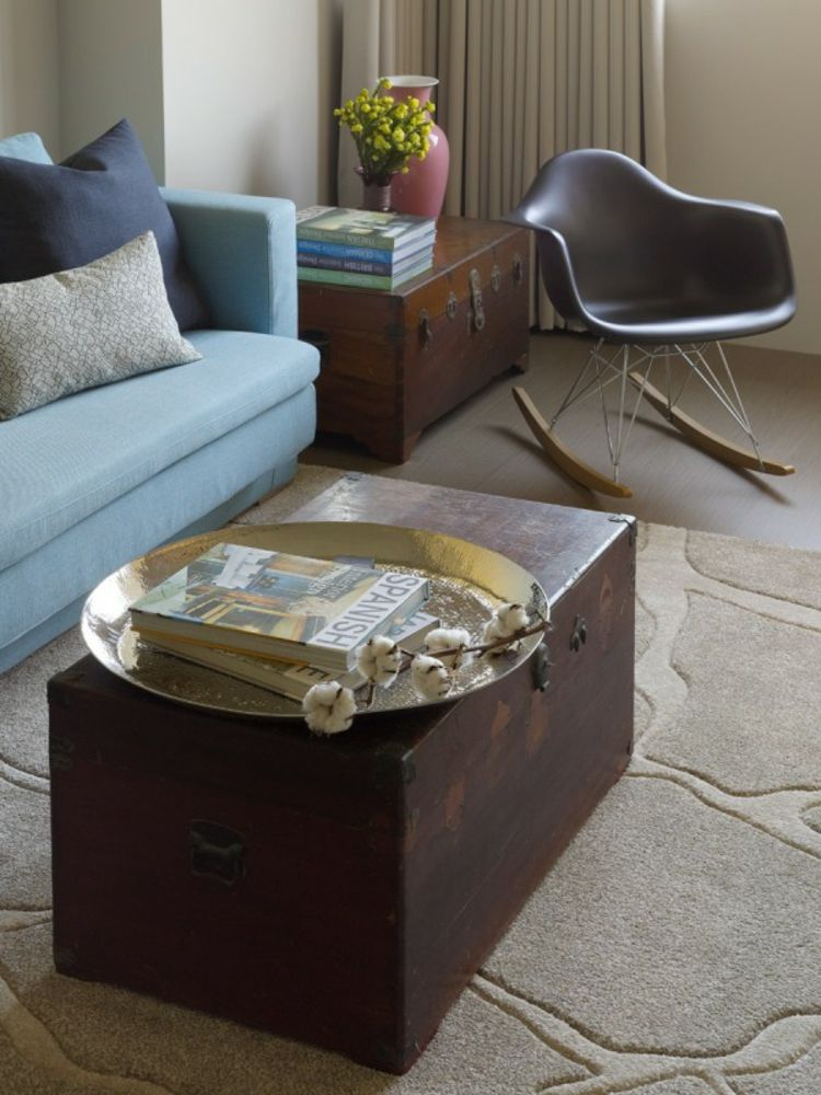 A modern taiwanese apartment a pair of vintage trunks repurposed as tables give additional storage and a creative feel the area rug though a neutral