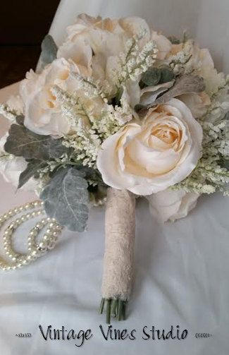 This pretty silk wedding bouquet is ready to ship. It is a very light blush pink and cream with accenting tallow berries and greenery for the perfect garden style wedding bouquet for your special day. Made with high quality silk flowers, the stems are wrapped in a vintage pink lace. The pearl drapery and few accent brooches help create a glamorous look without taking away from the garden style of this bouquet.  This bouquet measures approximately 10 inches wide and 15 inches in length…
