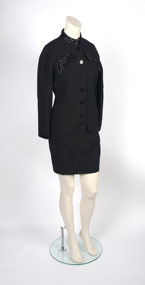 "Jean Muir Black Wool Evening Skirt Suit, 1980s. ""tailored jacket has mock collar, button front, breast pockets, collar and cuffs trimmed with black sequins, straight skirt, both fully lined, both labeled: Jean Muir."" Lot# 669---lot image"