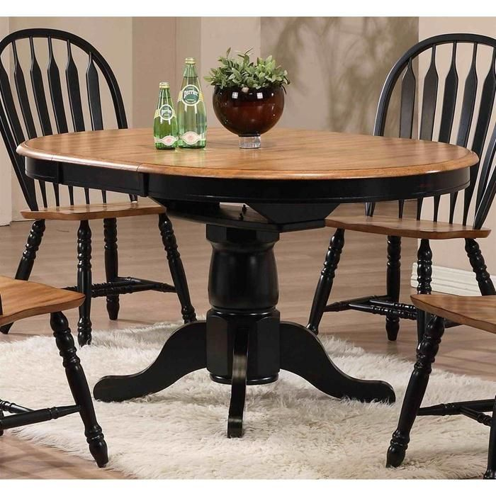 single pedestal dining table in deep rustic oak and black