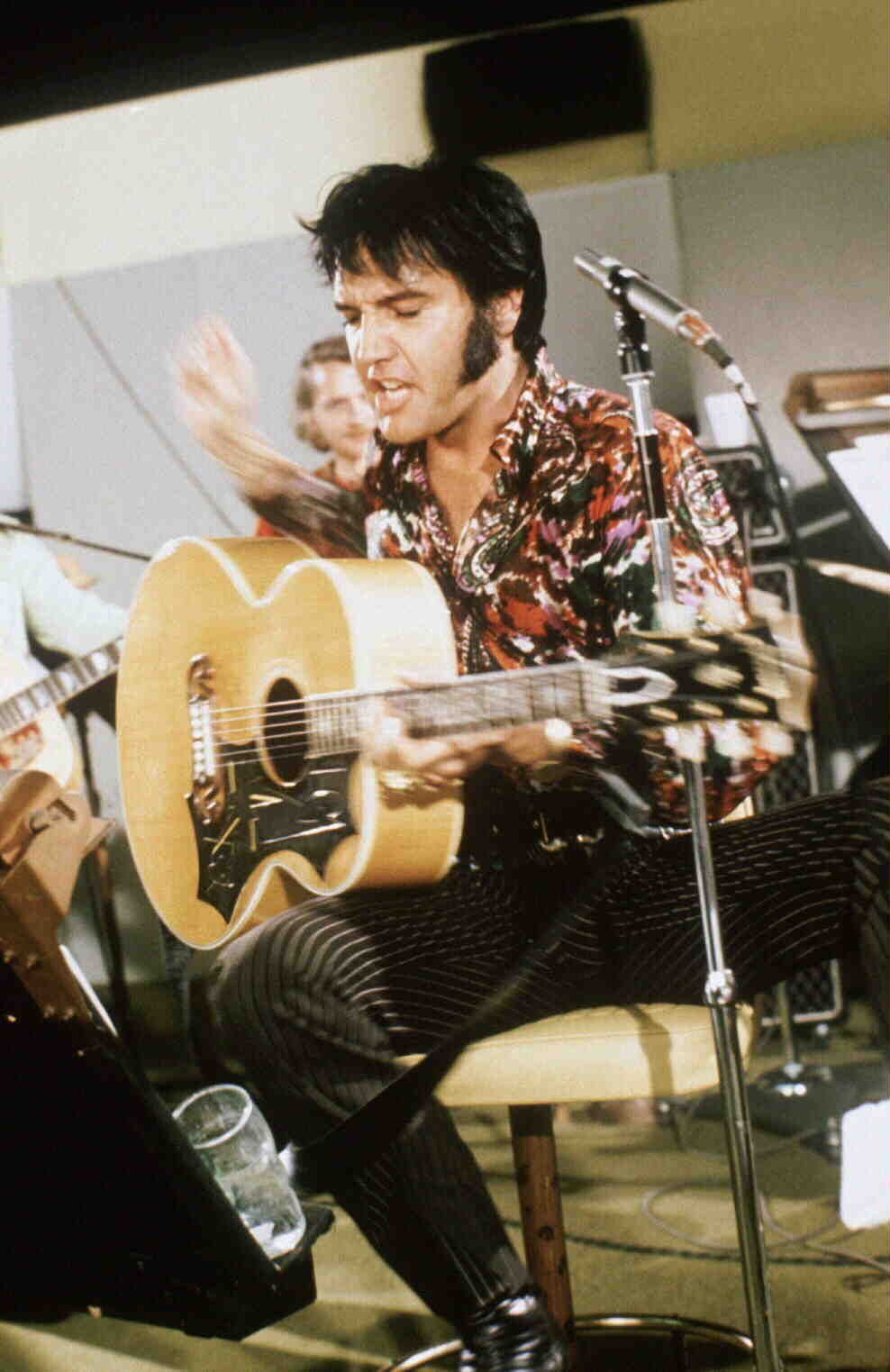 Full shot of elvis presley singing and playing guitar in