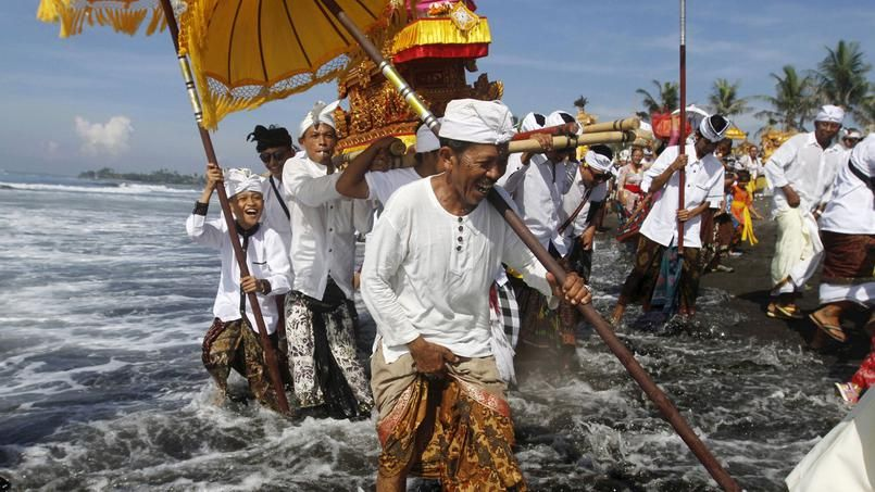 RITUEL SACRÉ. Sur la plage de Gianyar, sur l'île indonésienne de Bali, des hommes célèbrent Melasti, une très grande cérémonie de purification pour fêter le dernier jour du calendrier lunaire. Toutes les représentations des dieux du village, appelées « pratima », sont portées en procession jusqu'à la mer pour y être purifiées. Habillés de leur tenue traditionnelle et portant de magnifiques ombrelles jaunes, ces Balinais vont ainsi marcher pendant plusieurs kilomètres pour atteindre le…