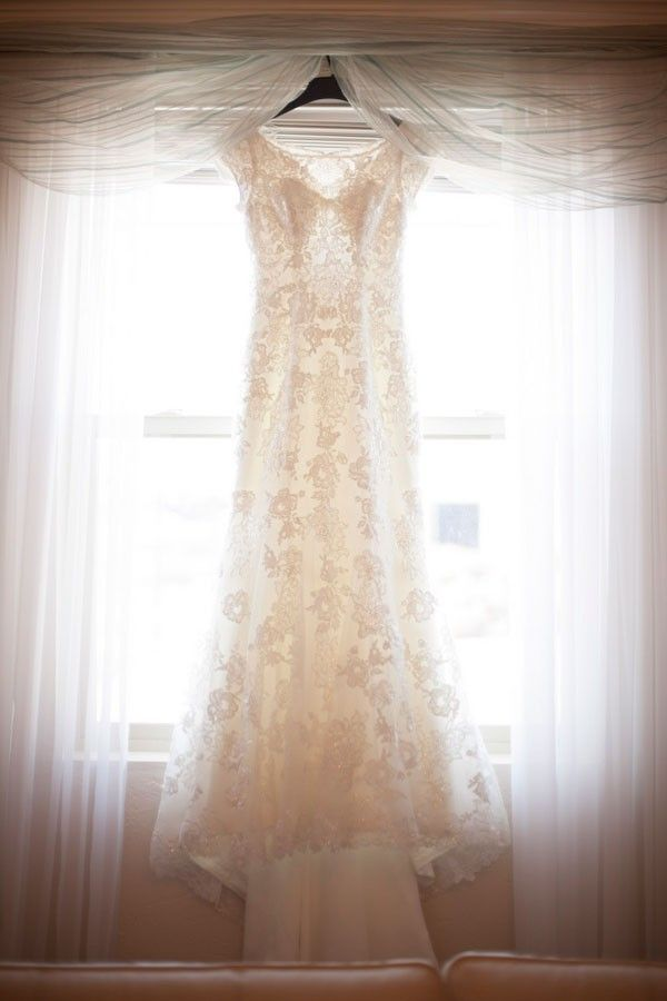 1d198c90543 Lace wedding dress hangs in window.