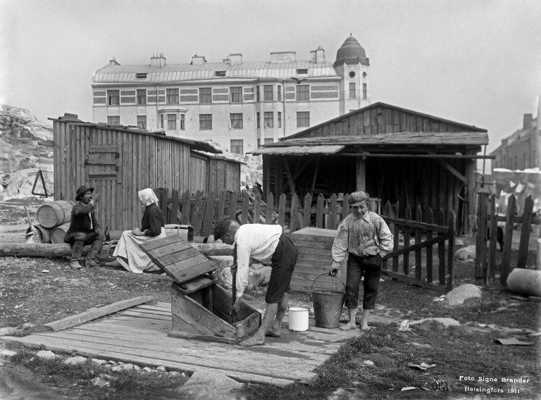 Pojat hakemassa vettä kaivosta Viides linja 5:ssä. Helsingin kaupunginmuseo Signe Brander 1911.