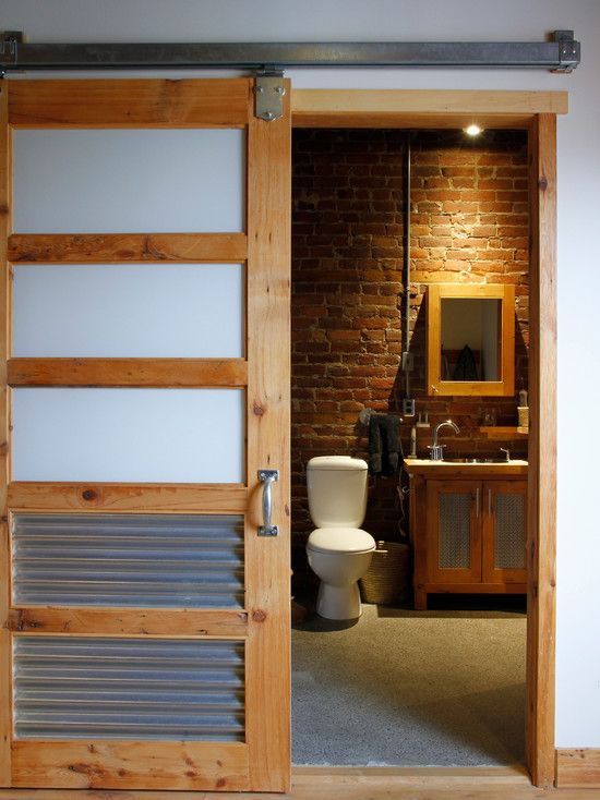 A Sliding Barn Door With Inset Frosted Glass And Corrugated Steel Panels Create A Charming And Rust Industrial Style Bathroom Eclectic Bathroom Bathroom Design