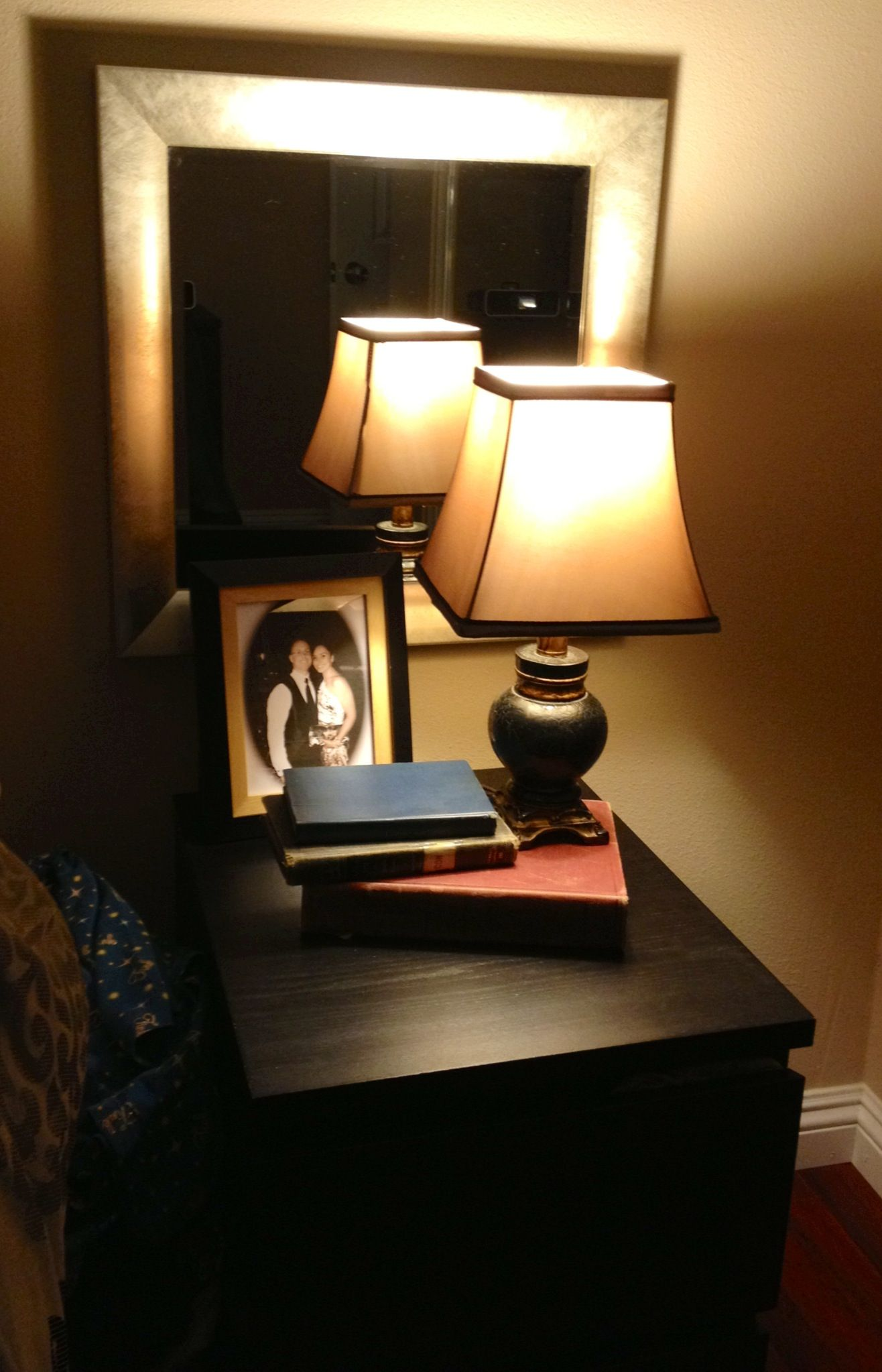 Mirror above night stands and lamps in front. Makes the