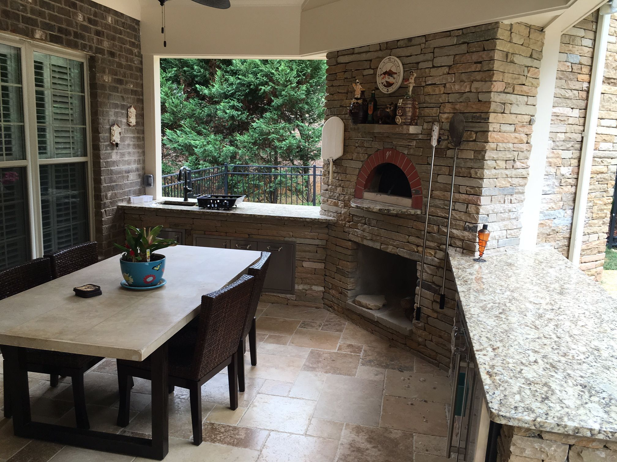 covered patio with an integrated outdoor fireplace and pizza oven