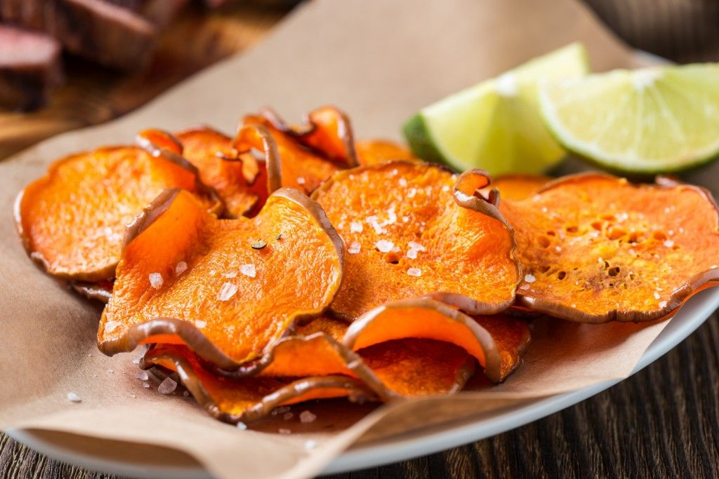Homemade organic baked pumpkin chips served with lime wedges on kraft paper #potatowedgesselbermachen