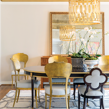 black and gold oval dining table with gold metal dining chairs