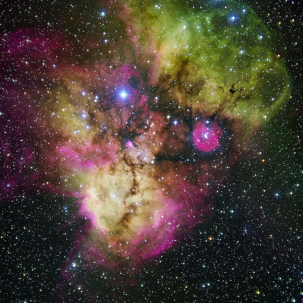 """Heart-Shaped Nebula  Area surrounding the stellar cluster NGC 2467, located in the southern constellation of Puppis (""""The Stern""""). With an age of a few million years at most, it is a very active stellar nursery, where new stars are born continuously from large clouds of dust and gas. The image, looking like a colourful cosmic ghost or a gigantic celestial Mandrill, contains the open clusters Haffner 18 (centre) and Haffner 19 (middle right: it is located inside the smaller pink region — the…"""