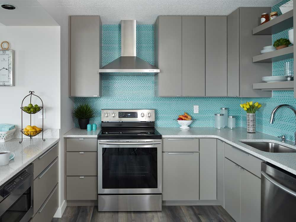 Corner View Of Condo Kitchen With Gray Slab Door Cabinets Ceiling High Aqua Glass Mosaic Tiles Stainless Range H Slab Door Kitchen Kitchen Slab Condo Kitchen