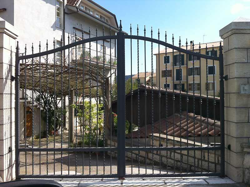 Cancello a doppia anta in ferro battuto con sistema di for Lance per cancelli in ferro