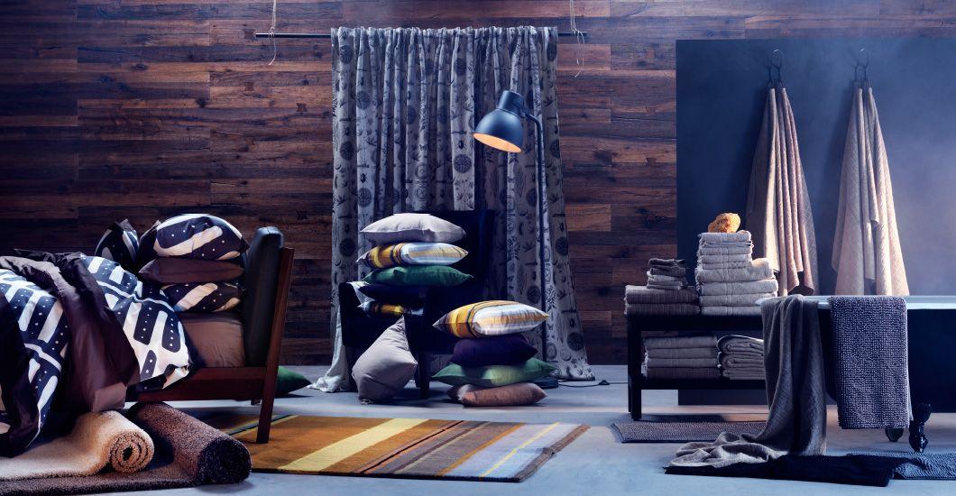 Diversos tejidos de colores otoñales, como cortinas, ropa de cama, toallas colgadas en la pared y apiladas en un banco y alfombras y cojines en el suelo.