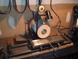 Surface Grinder - Homemade surface grinder adapted from a bench grinder and constructed from angle iron, threaded rod, wood, and steel.