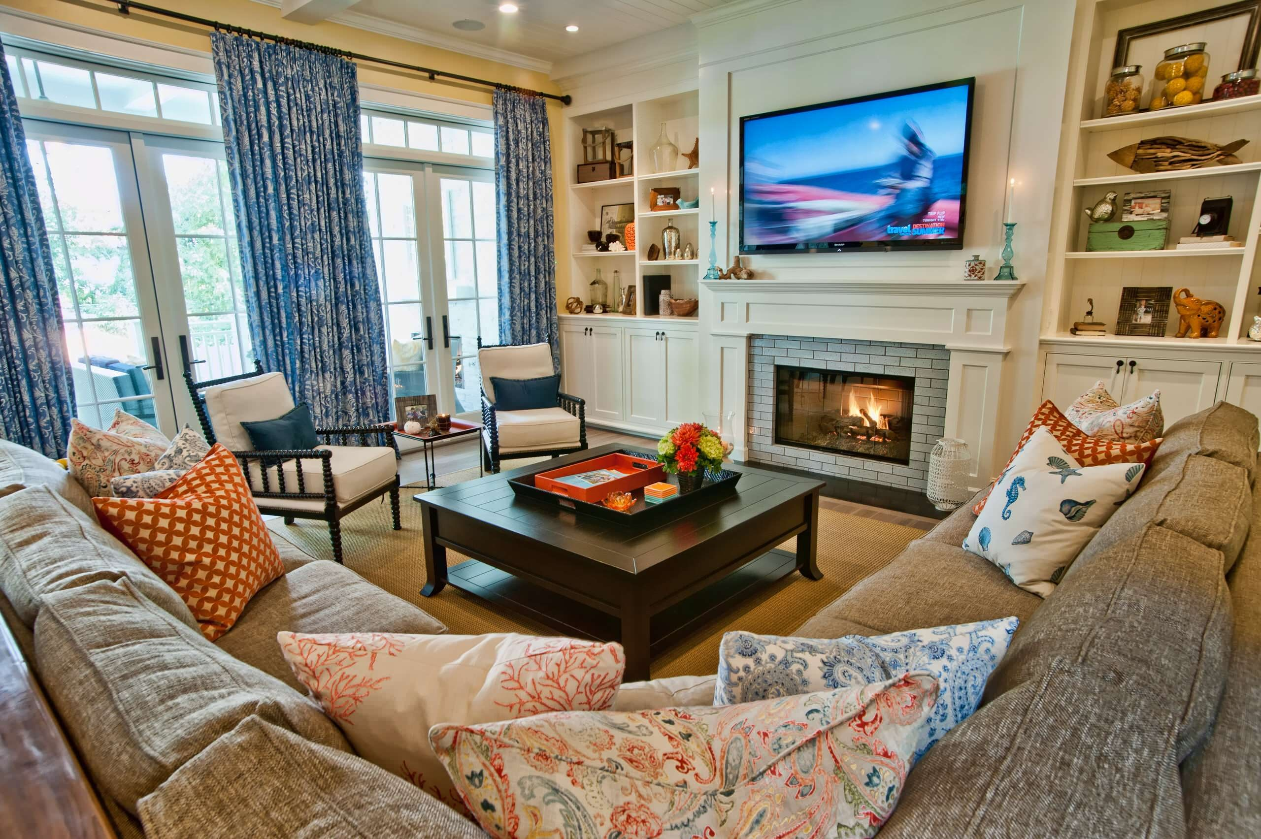 A tan sectional sofa and leather club chairs bine to create an
