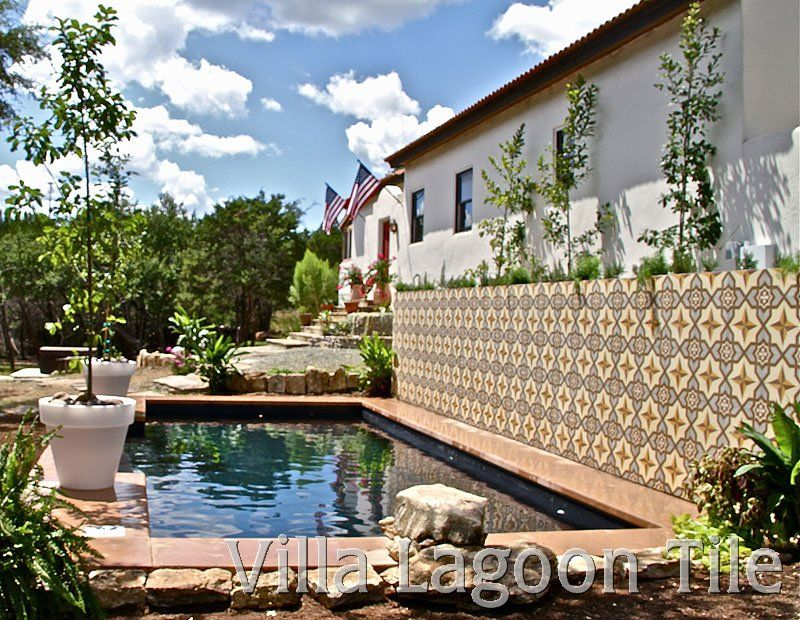 Cement tile on a garden wall adds interest to a swimming ...