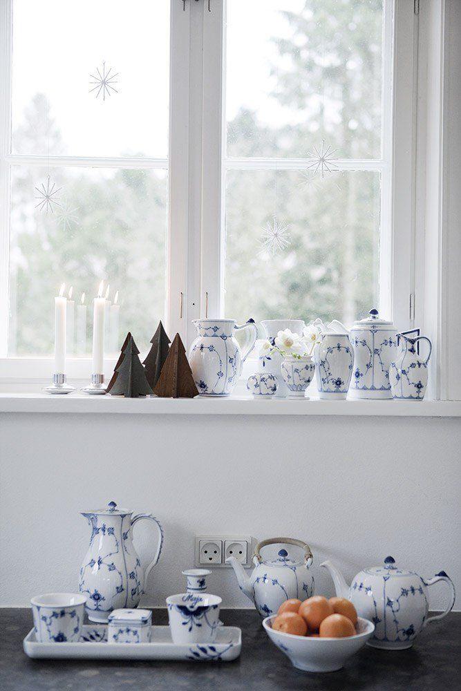 En fin samling af forskellige nye og antikke dele fra Royal Copenhagen pryder vindueskarmen. De er tilsat lidt jul i form af små metal- og træjuletræer fra Trip Trap og levende lys.