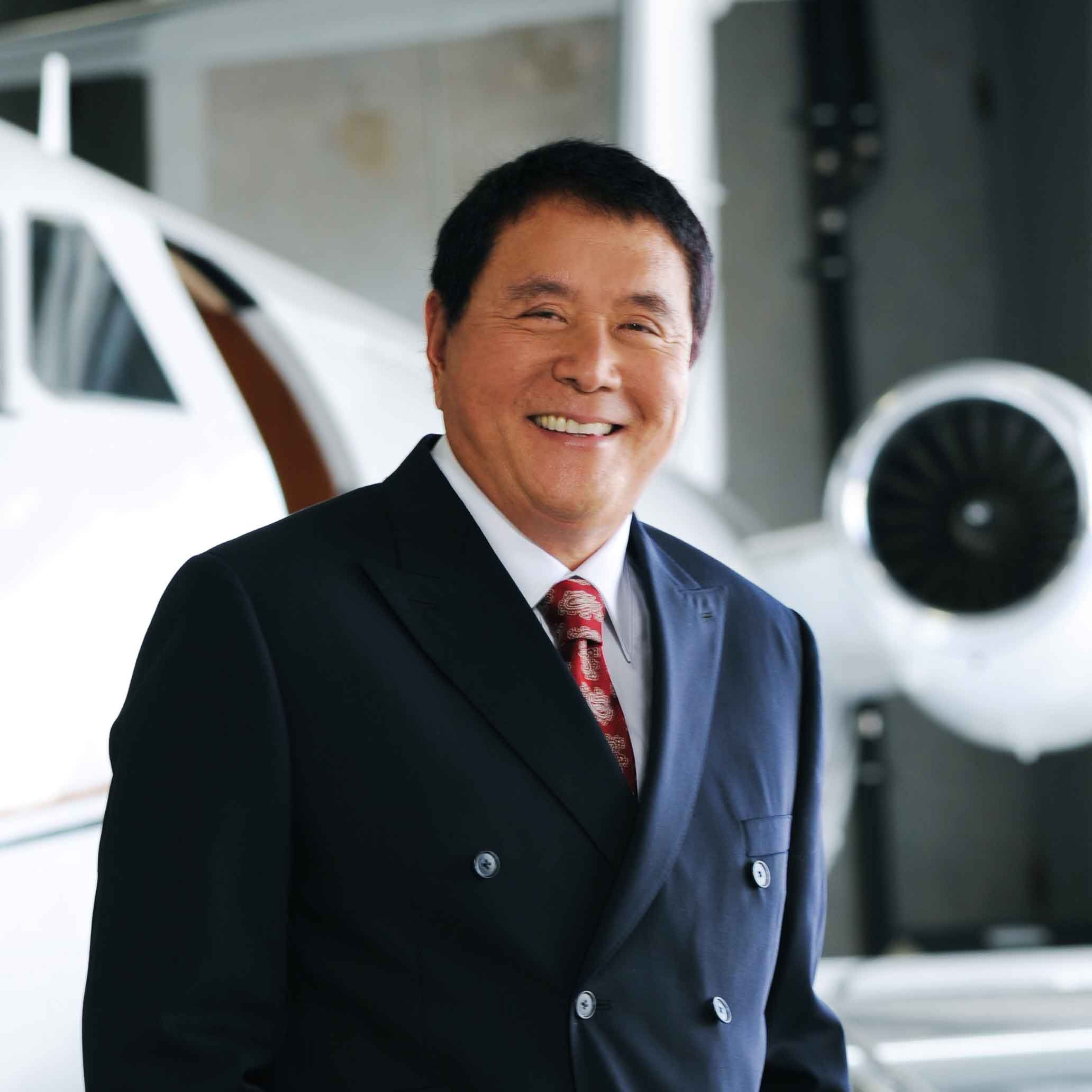 Robert Kiyosaki standing by a private jet in an airplane