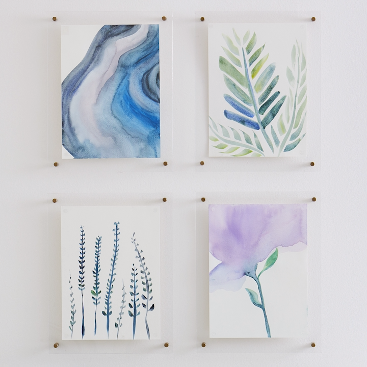 These DIY floating picture frames let you showcase your art while maintaining a minimalist vibe. Make one (or several!) using inexpensive acrylic sheets. #cheapdiy #diyframes #diywallart #bhg
