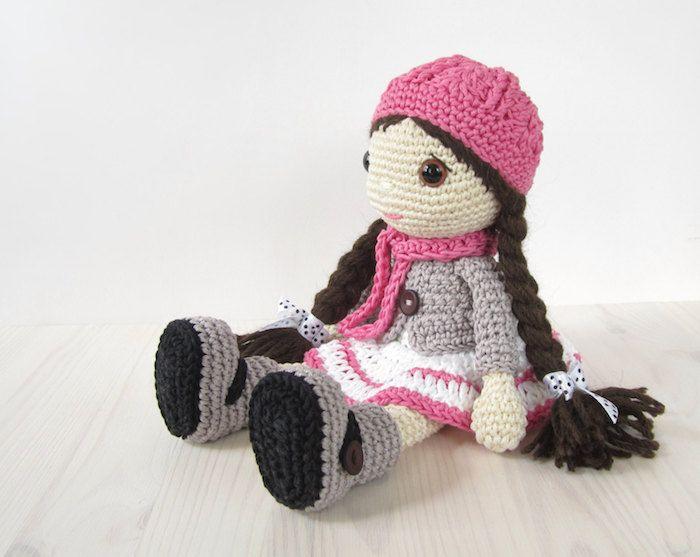 eine niedliche Puppe mit rosa Schal und Hut, lange braune Zöpfe ...