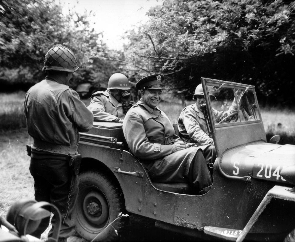 Dwight Eisenhower, smiling at his jeep in an orchard. Sitting in the back, General Bradley.