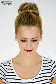 Top knot with natural makeup and a dark lip.