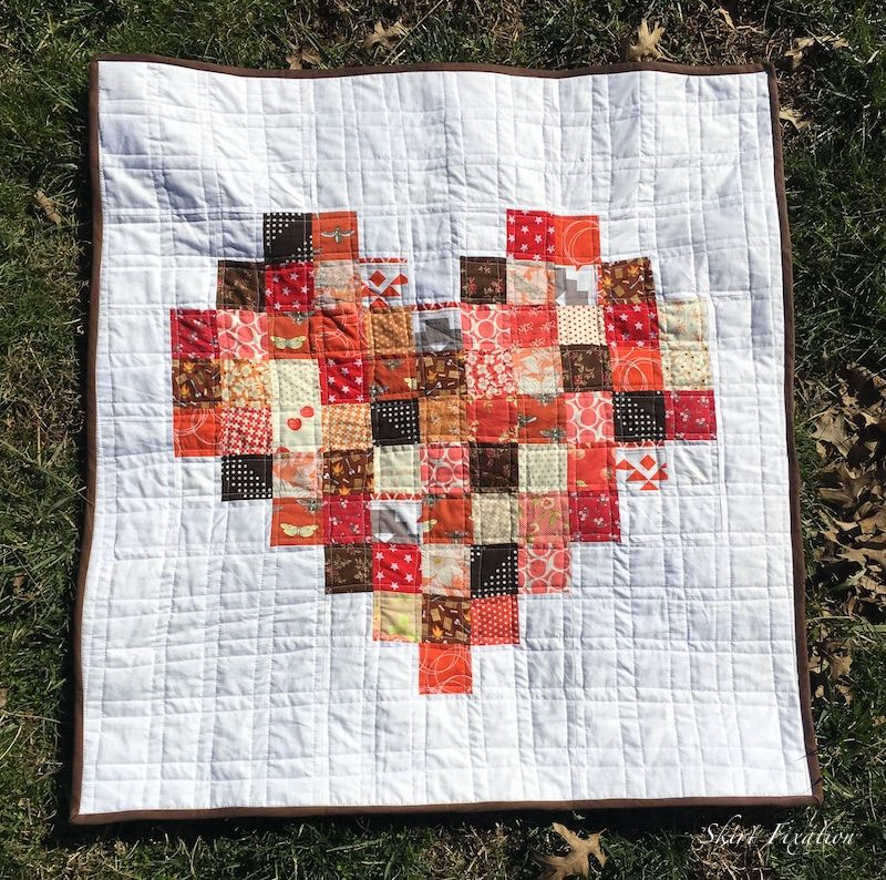 Our 8 year old in house seamstress sewed a pixelated heart baby quilt for our expected baby! She is here to tell you all about sewing this baby quilt.