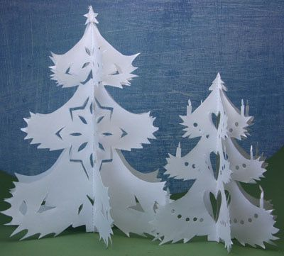 Cut paper trees made from white paper create a winter scene.