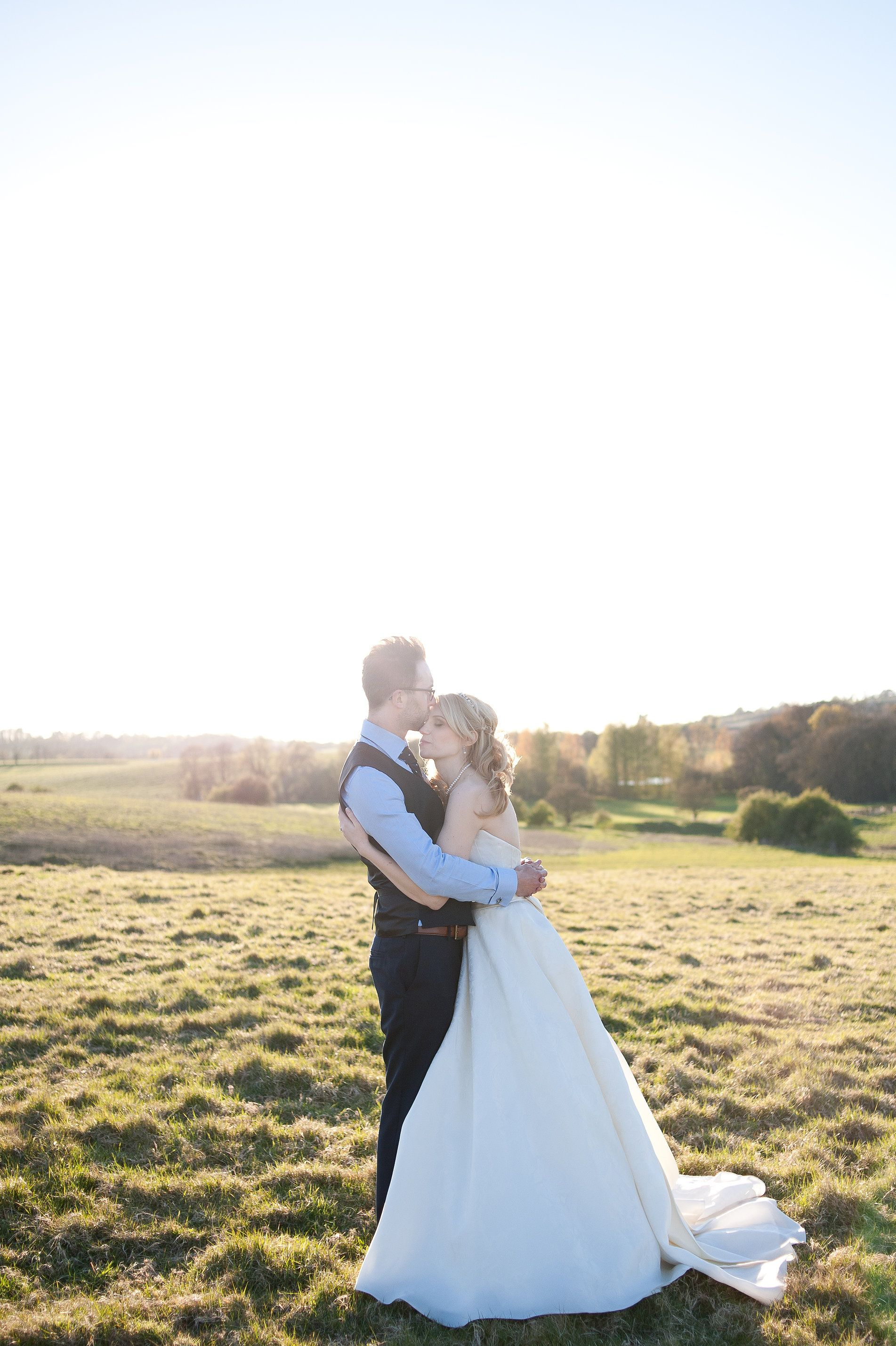 Bride in sassi holford dress in field at sunset for classic english