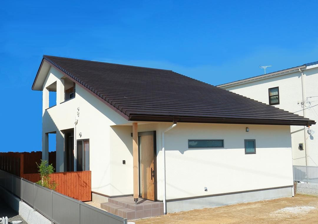 済んだ空に映えるダークブラウンの 大きな屋根と白い壁の家 外観