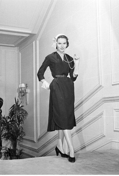 Sylvie Hirsch in Dior's black Alpaca apron dress over pleated skirt, worn with banana yellow cap, photo by Walter Carone,