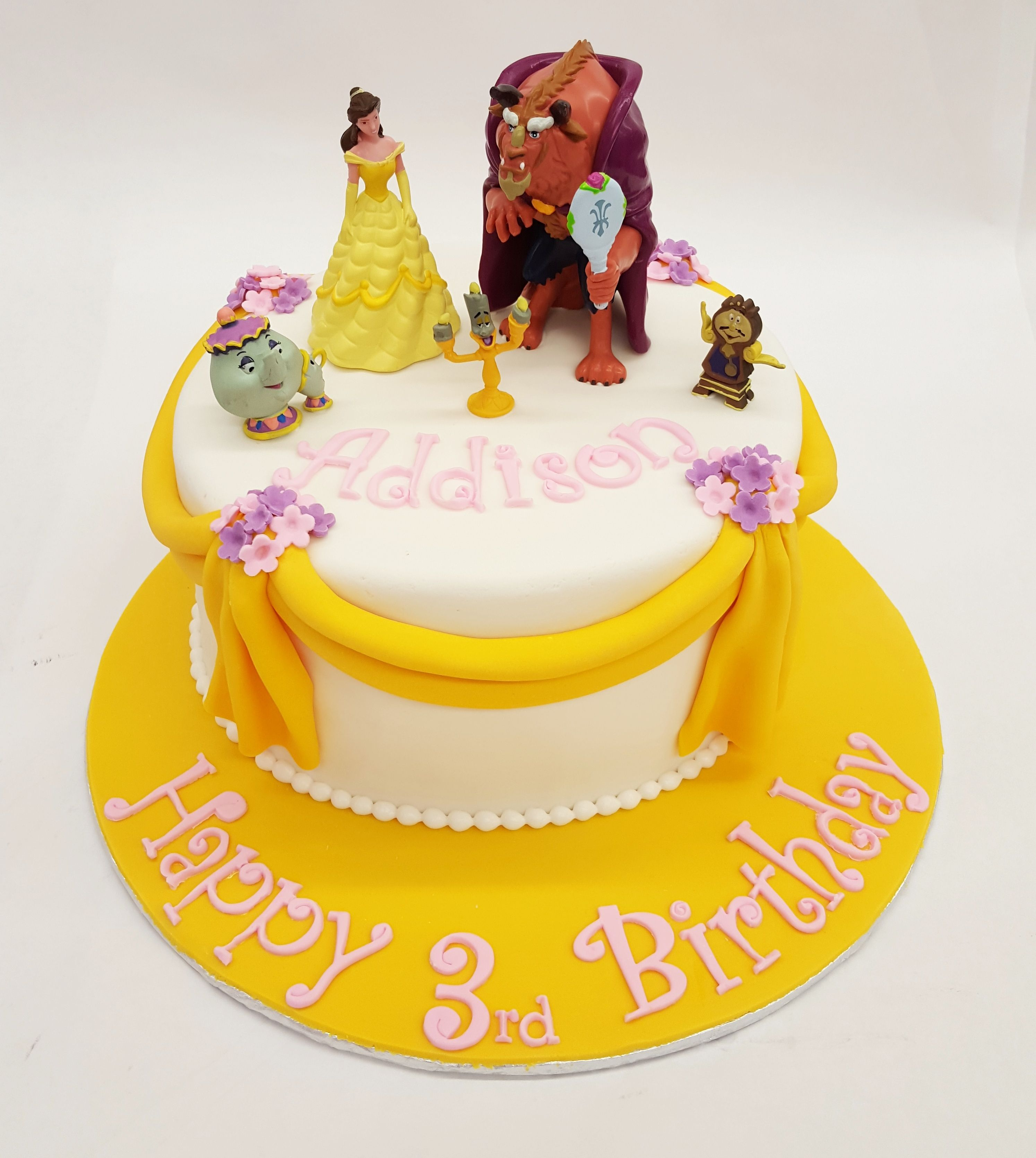 A Beauty and the Beast cake with draped fondant and little flowers