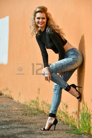 6047360c5a49 Glamour fashion model with perfect slim body wearing cropped top and ripped  jeans posing sexy outsid Stock Photo