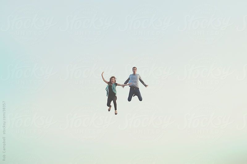 Young happy couple floating in air by Rob Campbell