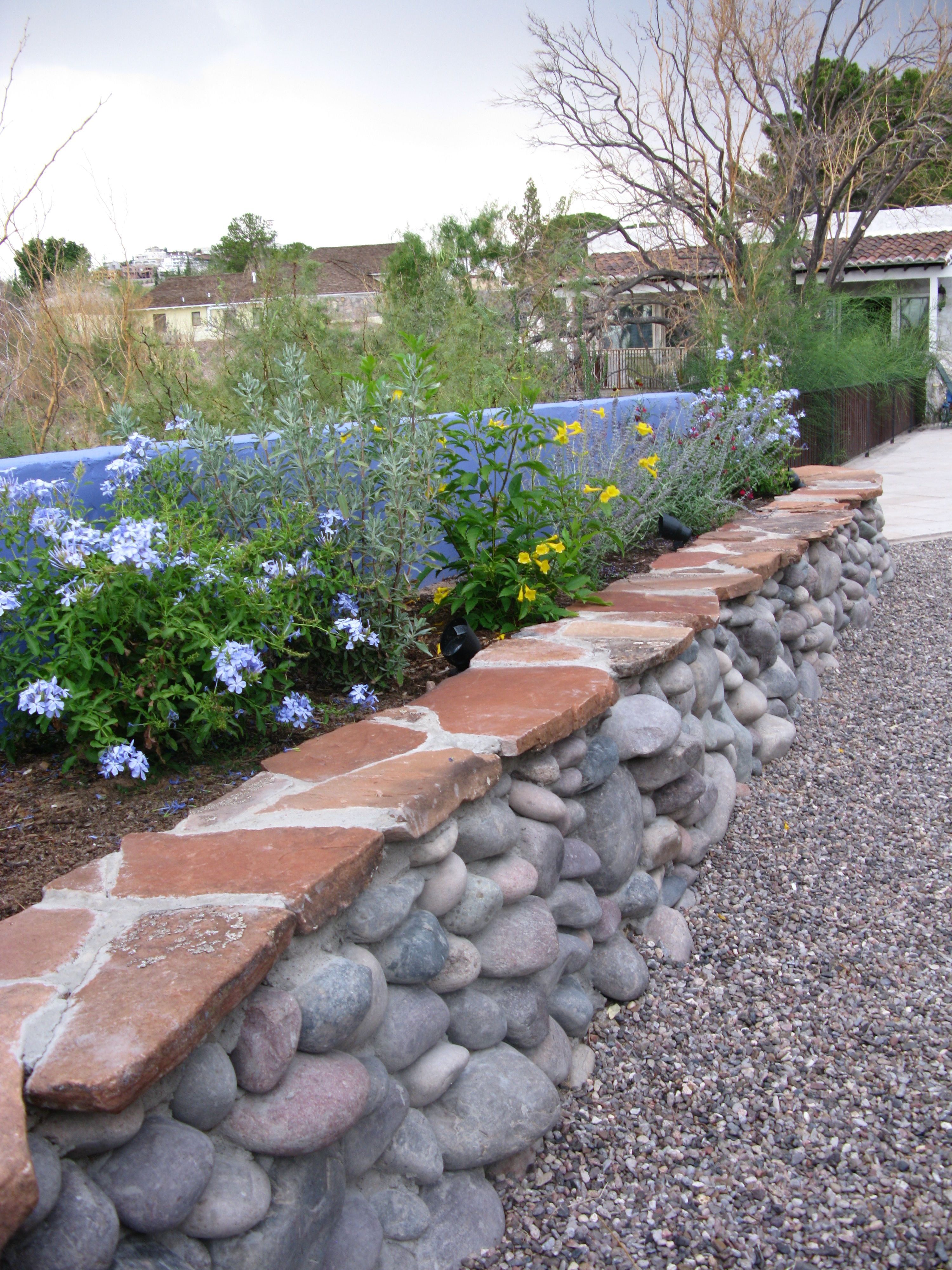 Desert flower bed made from flagstone and river rock that