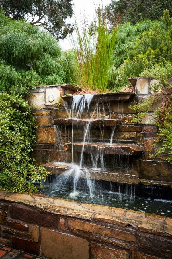natural look waterfall cascade green landscape outdoor area natural stone wall…