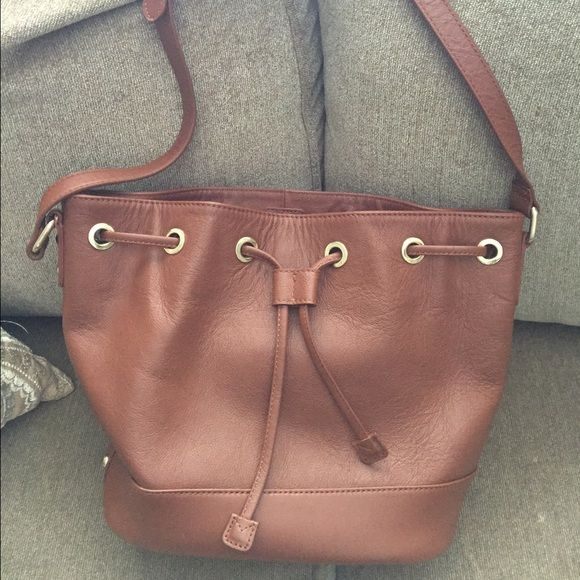 Genuine leather cross-body bucket bag Beautiful cognac brown leather bucket bag! In excellent condition with no damage at all inside or out. Only carried once. The brand is Massi and it has protective feet on the bottom as well as an interior zip pocket and two slip pockets. Massi Bags Crossbody Bags