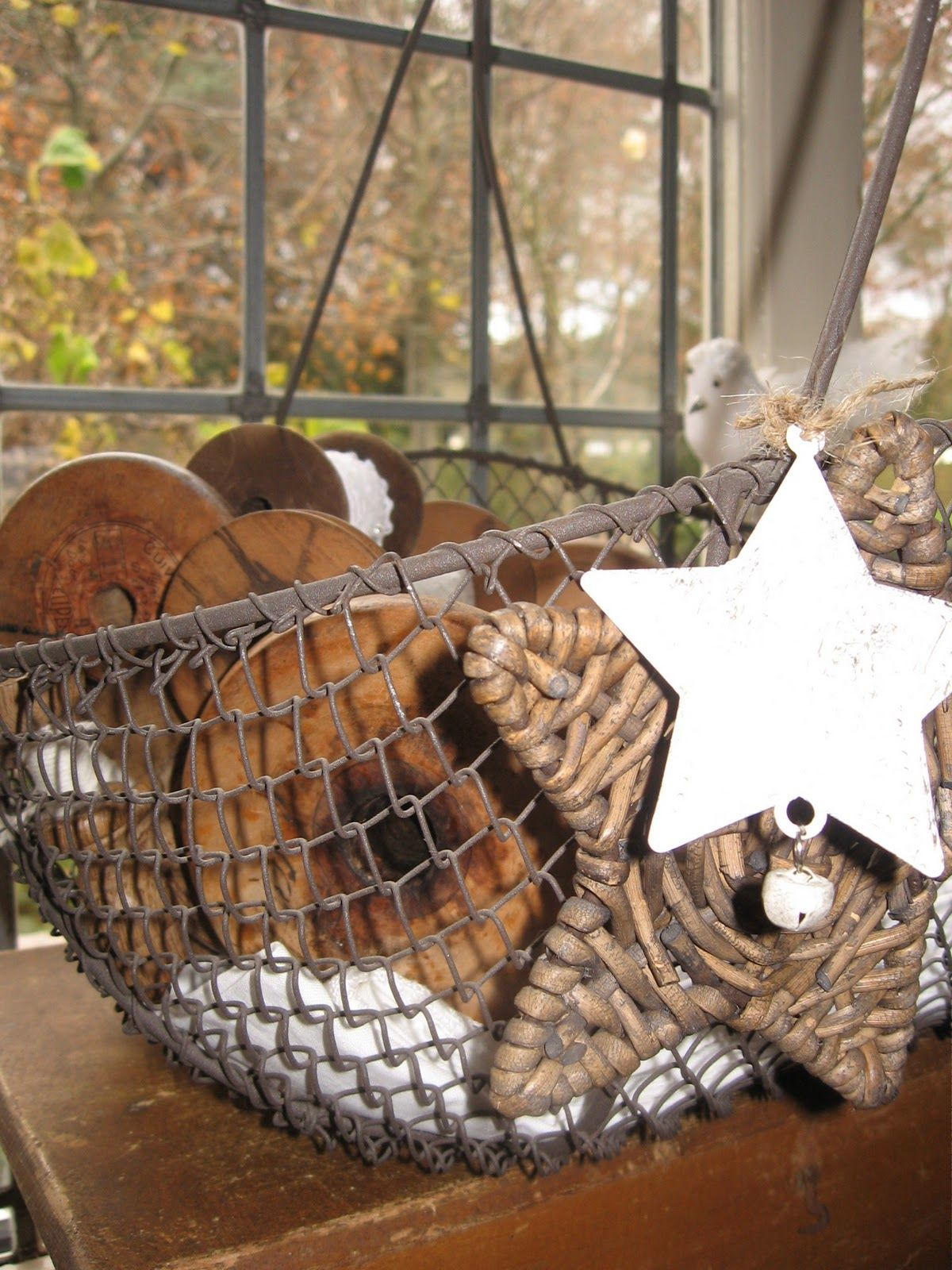 Star decorations in wire basket full of large wooden spools | wire ...