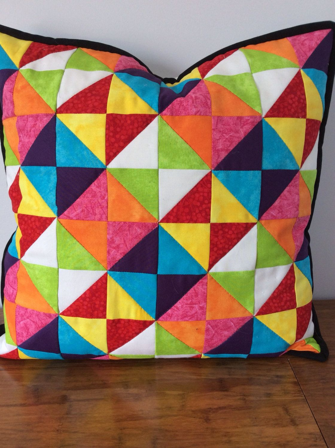 Handcrafted patchwork cushion cover.  Quilted Multicoloured patchwork cushion cover.  Has a white back with centre zip and black binding.